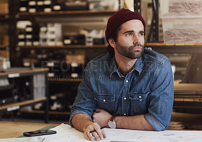 Buy stock photo Shot of a young businessman designing a blueprint in a creative office