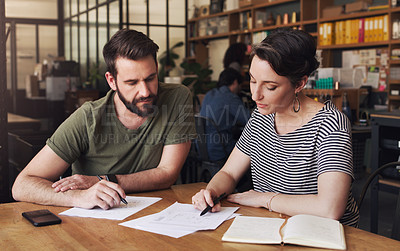 Buy stock photo Shot of a young businessman and businesswoman designing a blueprint in a creative office