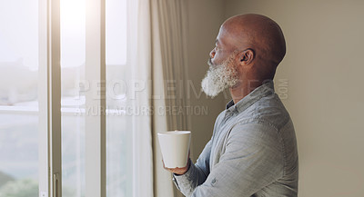 Buy stock photo Cropped shot of a contemplative senior man standing alone in his home and enjoying a cup of coffee