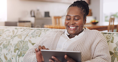 Buy stock photo Cropped shot of a happy senior woman sitting alone in her living room and using a tablet