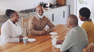 Buy stock photo Cropped shot of a happy family sitting together and enjoying cups of coffee with biscuits in their kitchen