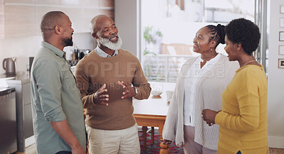Buy stock photo Cropped shot of a happy family standing together in their home and having a discussion