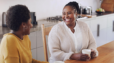 Buy stock photo Cropped shot of a happy senior woman sitting in the kitchen with her daughter and enjoying a cup of coffee