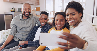 Buy stock photo Cropped portrait of an attractive young woman using her cellphone to take a selfie with her family at home