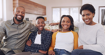 Buy stock photo Cropped portrait of a happy young family sitting together on the sofa at home during a weekend off