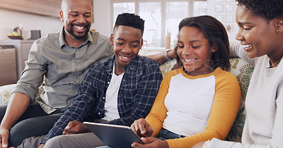 Buy stock photo Cropped shot of a happy young family sitting and using technology during a weekend off at home