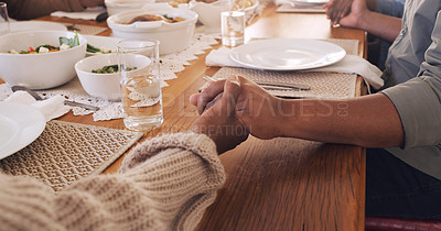 Buy stock photo Cropped shot of an unrecognizable family sitting and holding hands while praying before having lunch in their home