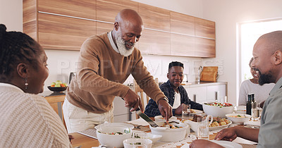 Buy stock photo Cropped shot of a happy senior man standing and serving lunch for his family during a day off at home