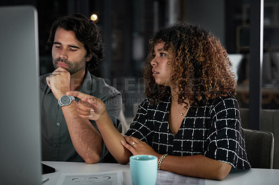 Buy stock photo Cropped two of two young businesspeople working together on a computer inside their office at night