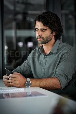 Buy stock photo Cropped shot of a handsome young businessman using his cellphone while working late in his office at night