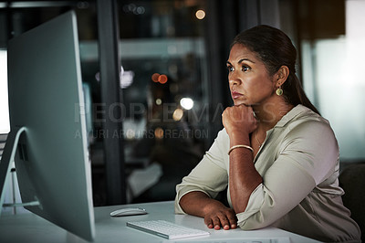 Buy stock photo Cropped shot of an attractive mature businesswoman working on a computer inside her office at night