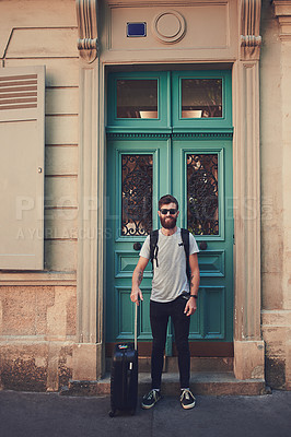 Buy stock photo Shot of a handsome young man standing with his luggage on the sidewalk in a foreign city