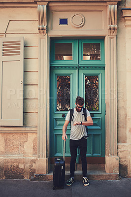 Buy stock photo Shot of a handsome young man standing with his luggage on the sidewalk in a foreign country
