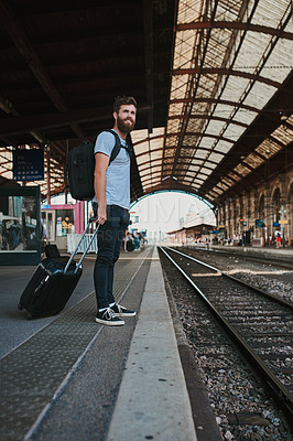 Buy stock photo Shot of a man carrying luggage while waiting for his train