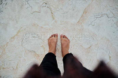 Buy stock photo Cropped shot of an unrecognizable traveller standing with her feet in the sand