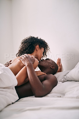 Buy stock photo Cropped shot of an affectionate young couple making lover under the covers in their bedroom at home