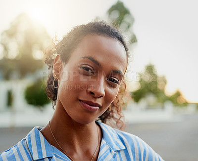 Buy stock photo Cropped portrait of an attractive young woman standing outside alone during a day off