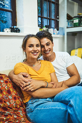 Buy stock photo Portrait of a cheerful young couple holding each other while being seated on a sofa inside at home during the day