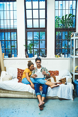 Buy stock photo Shot of a cheerful young couple browsing on a digital tablet together while being seated on a sofa inside at home