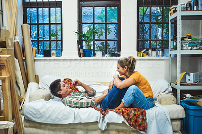 Buy stock photo Shot of a cheerful young couple relaxing together on a sofa inside at home during the day