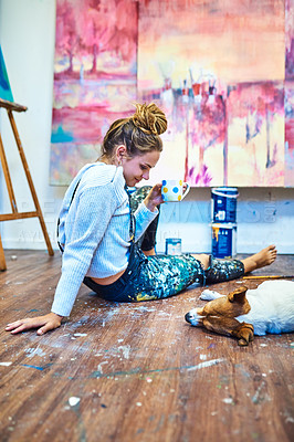 Buy stock photo Full length shot of an attractive young female painter admiring her sleeping dog while having coffee in an art studio