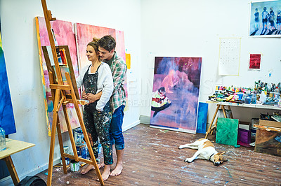 Buy stock photo Full length shot of an affectionate young man embracing his girlfriend from behind while she's painting on a canvas in an art studio
