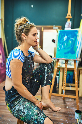 Buy stock photo Cropped shot of an attractive young female painter looking at her painting in her art studio