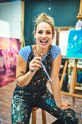 Buy stock photo Cropped portrait of an attractive young female painter smiling while holding her paint brush in her art studio