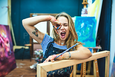 Buy stock photo Cropped shot of an attractive young female painter making a funny face while sitting in her art studio