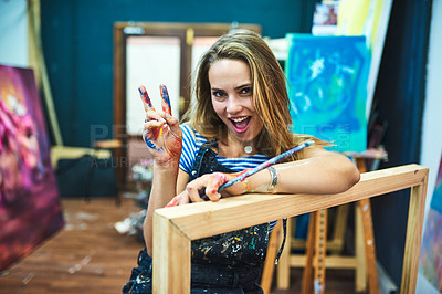 Buy stock photo Cropped portrait of an attractive young female painter showing the peace sign while sitting in her art studio