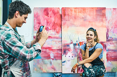 Buy stock photo Cropped shot of an unrecognizable man using a cellphone to take pictures of his attractive girlfriend in her art studio