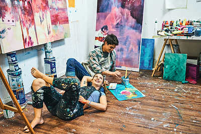 Buy stock photo Full length shot of an affectionate young couple sitting on the floor together in an art studio during the day