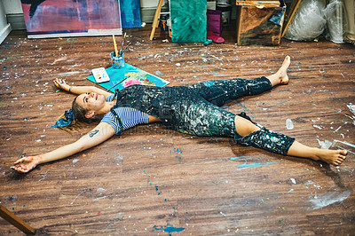 Buy stock photo Full length shot of an attractive young woman feeling playful while lying down on the floor in her art studio