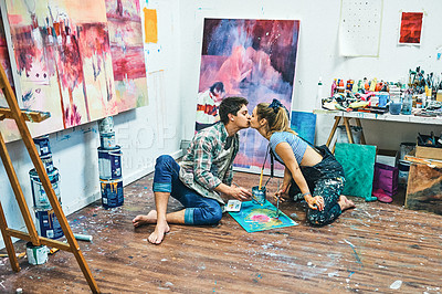Buy stock photo Full length shot of an affectionate young couple sitting together and kissing while painting in their art studio