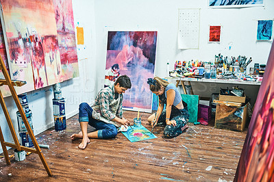 Buy stock photo Full length shot of a young couple sitting together and painting on the floor of an art studio