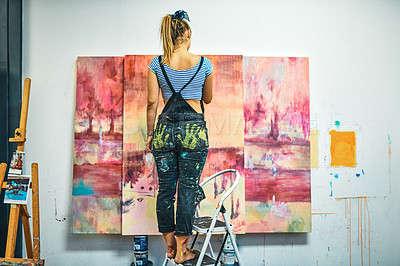 Buy stock photo Full length shot of an unrecognizable woman standing on a ladder and painting in her art studio
