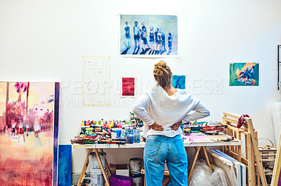 Buy stock photo Rearview shot of an attractive young woman looking at the paintings inside her art studio