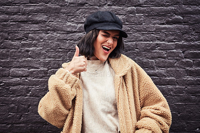 Buy stock photo Shot of a beautiful young woman giving thumbs up against a grey wall in the city