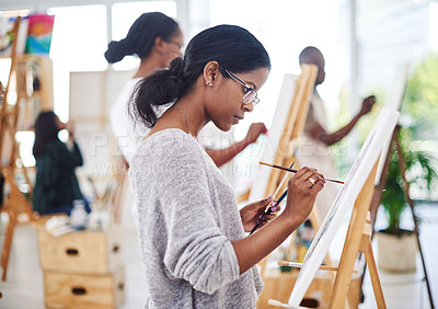 Buy stock photo Shot of a beautiful young woman working on a painting in a art studio