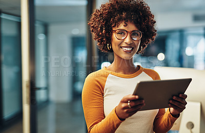 Buy stock photo Cropped portrait of an attractive young businesswoman working on her tablet in the office
