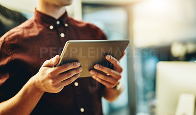 Buy stock photo Cropped shot of an unrecognizable young businessman working on his tablet in the office