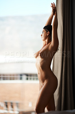 Buy stock photo Cropped shot of a sexy young woman looking out the window while posing nude in her bedroom