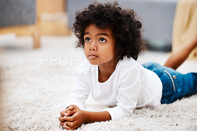 Buy stock photo Cropped shot of an adorable little boy lying down on a carpet and watching tv at home