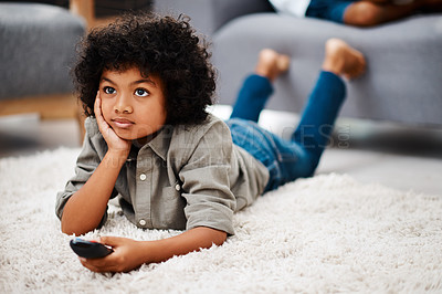 Buy stock photo Full length shot of an adorable little boy lying down on a carpet and watching tv at home
