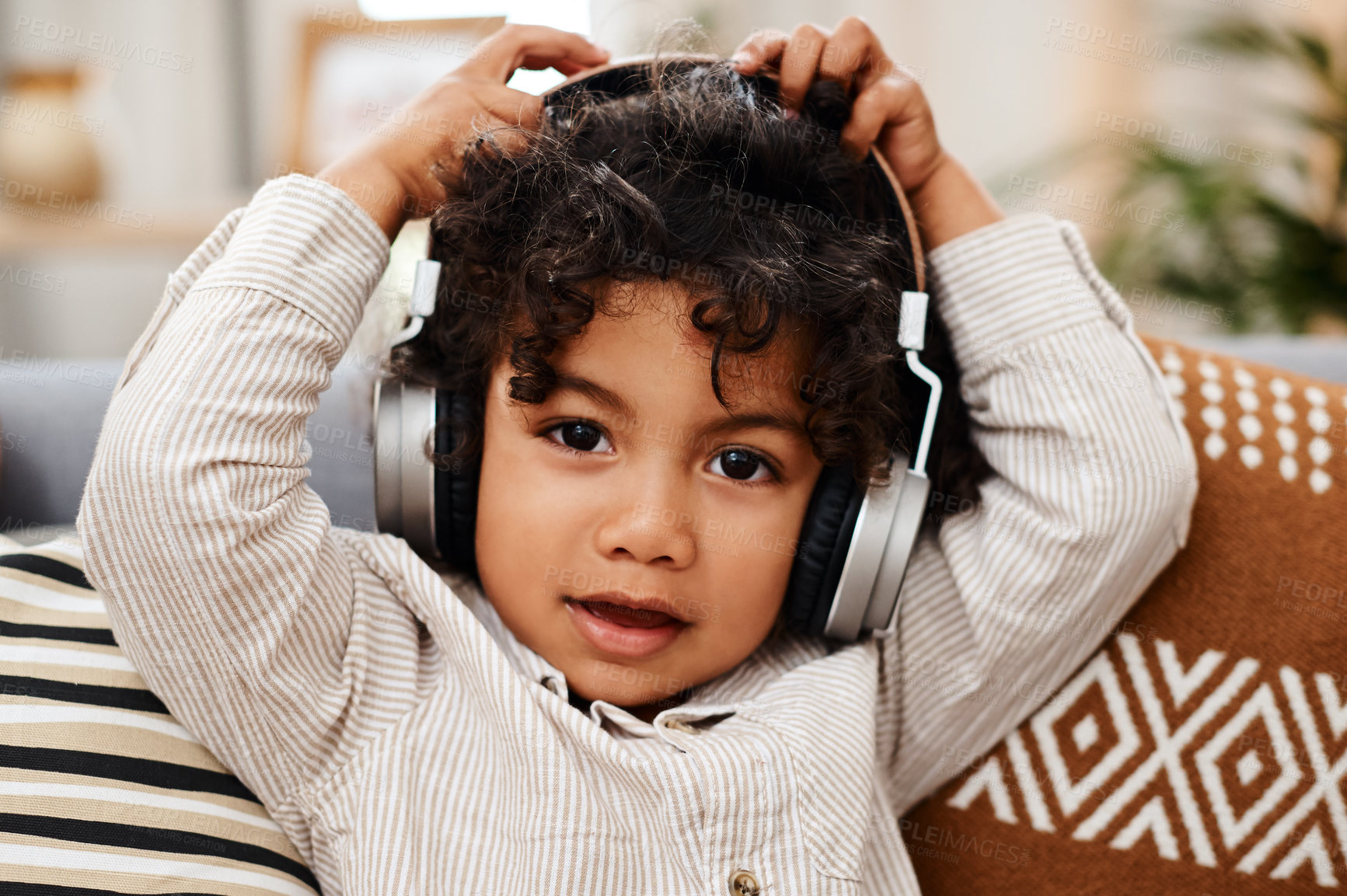 Buy stock photo Portrait of an adorable little boy listening to music on headphones while sitting on a sofa at home