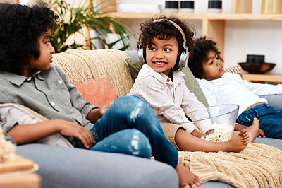 Buy stock photo Shot of an adorable little boy listening to music on headphones while spending time with his brothers at home