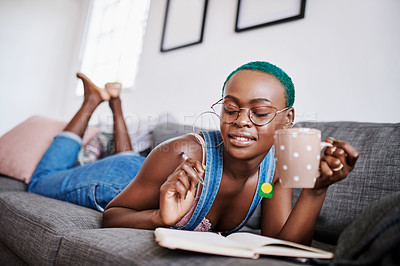 Buy stock photo Shot of a young woman writing in a notebook while drinking tea at home