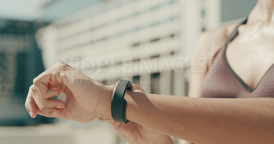 Buy stock photo Closeup shot of an unrecognisable woman checking her watch while exercising in the city
