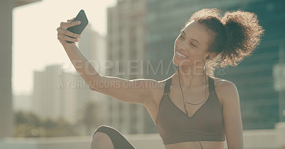 Buy stock photo Shot of a sporty young woman taking selfies in the city