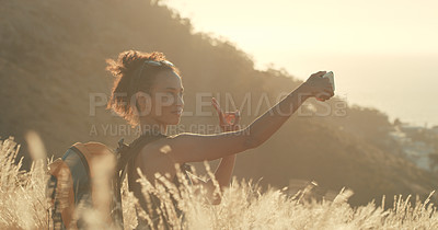 Buy stock photo Shot of a young woman taking selfies while out on a hike